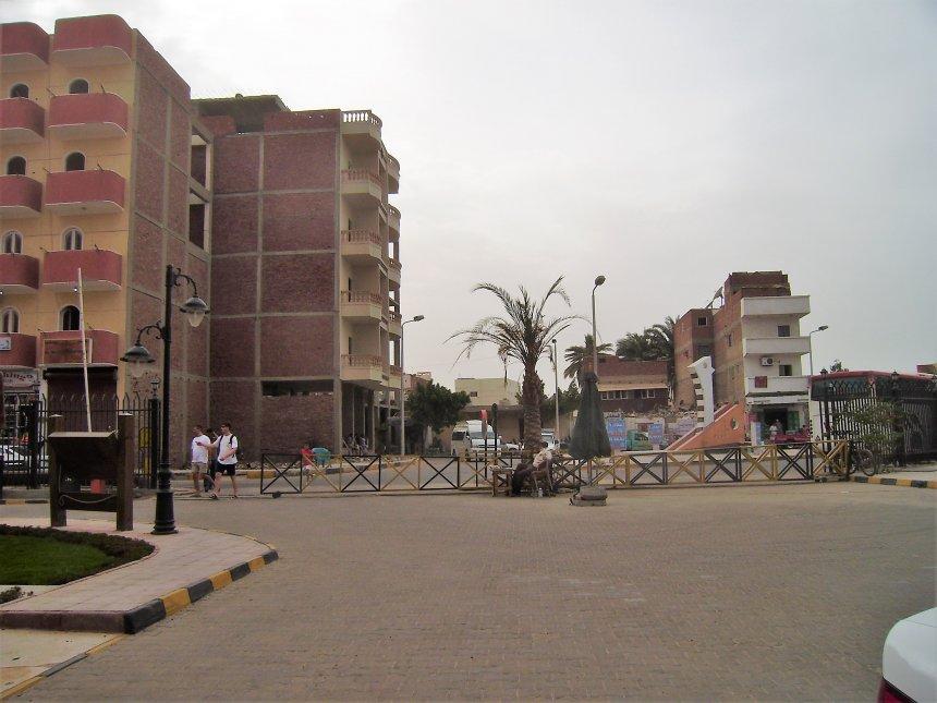 Hurghada. Een van de drie toegangen tot het toeristencomplex. De bewakers zitten in het midden, buik vooruit, onder het palmboompje