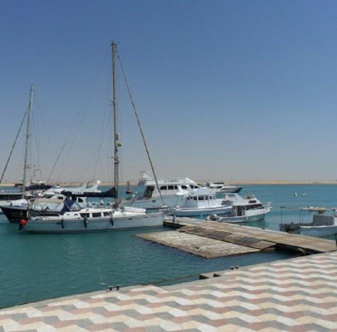 Dulce aan de steiger van de Suez Yacht Club (voordat ze gekeerd werd) Op de achtergrond het Suezkanaal, waar geen zeeschip vaart