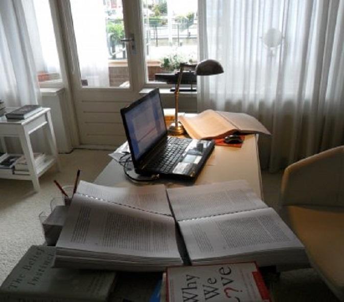 Mijn bureau met de drie opengeslagen correctieexemplaaren van mijn boek