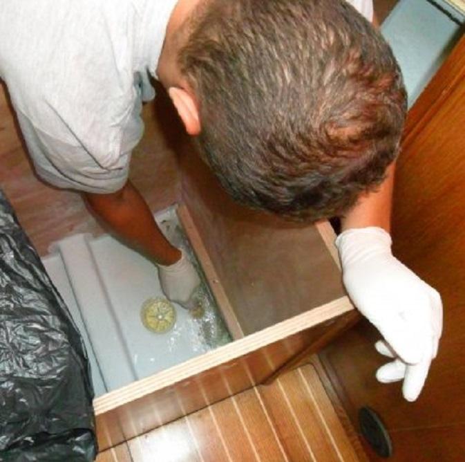 Kostas repareert met glasvezelmatjes en epoxy de zwakke plek onder het bed in de voorhut