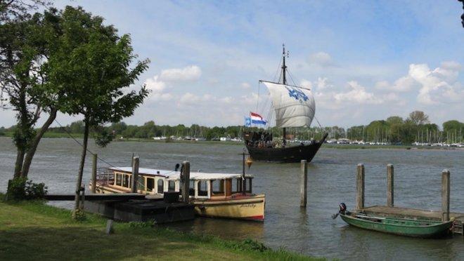 De Kamper Kogge onder zeil op de IJssel voor Kampen. Op de achtergrond de jachthaven van Seveningen, waar we liggen. (foto: kamperkogge.nl)