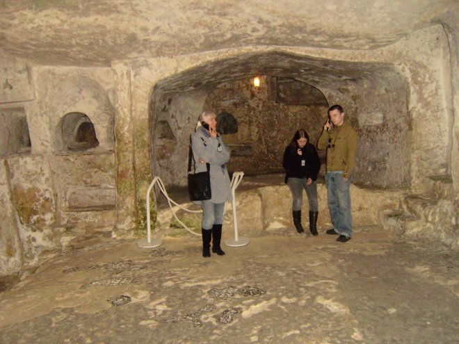 Ans, Esther en Rommert in de St Pauls Catacombs, luisterend naar de audioguide